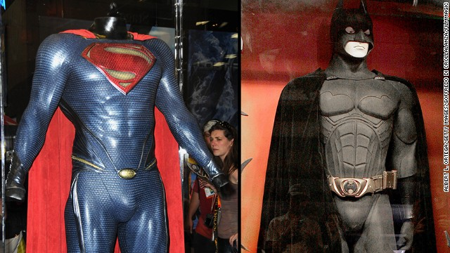 "The Superman costume from ""Man of Steel"" and the Batman costume from ""Batman Begins"" are displayed in cases"