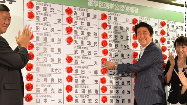 Japan's PM Shinzo Abe smiles as he places a rose on an LDP candidate's name to indicate an election win on July 21, 2013.