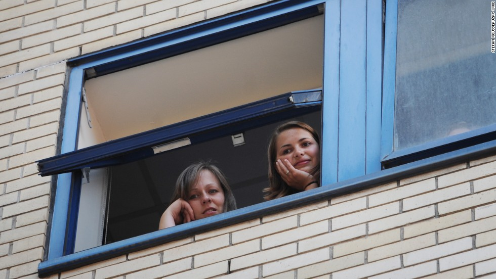 Hospital staff look out over a gathering crowd at St. Mary's Hospital in London on July 22.