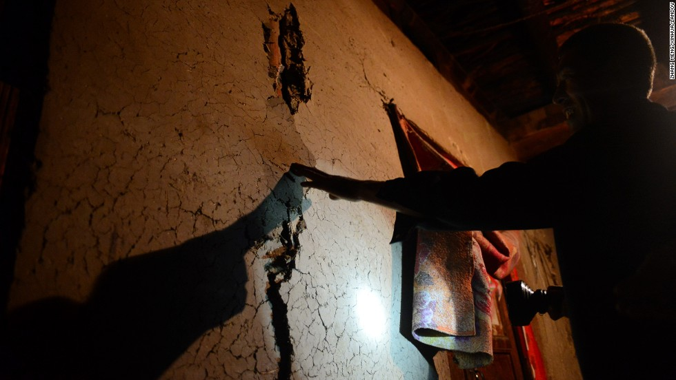 Hou Xuming examines the cracks in his house at Hadiha on July 23.