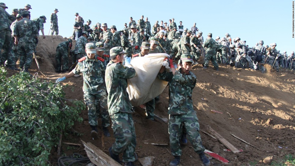 Military personnel work on a hillside in Yongguang in Minxian County on Monday, July 22.