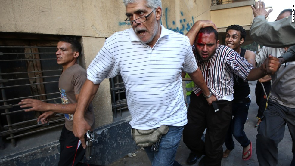 A man with a pistol and other Morsy opponents detain a suspected Morsy supporter who was wounded during clashes in Cairo on Monday, July 22. Supporters and opponents clashed near the city's Tahrir Square.