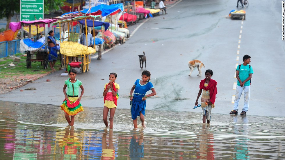 People cross a flooded road near the Triveni Sangam in Allahabad, India, on July 22. According to Hindu tradition, a bath at the confluence of three rivers -- the Ganges, the Yamuna and the mythical Saraswati -- atones for sin.