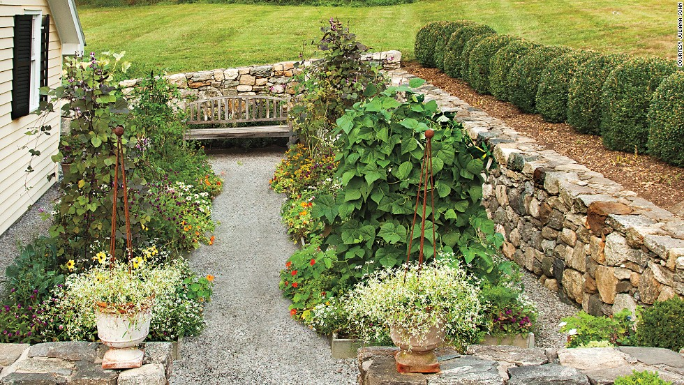 Low stone walls frame the entrance to the kitchen garden, which used to be a driveway. The garden is organized in a tidy grid; convenient paths around the beds make harvesting simple.