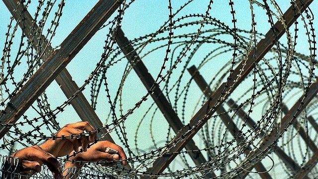 (FILES) Iraqi detainees rest their hands on razor wires as they watch a group of freed prisoners leaving the Abu Ghraib prison on the outskirts of Baghdad, in this September 16, 2004 photo. A US defense contractor accused of helping torture prisoners at Iraq's infamous Abu Ghraib prison has paid former detainees more than $5 million to settle a lawsuit, according to regulatory filings obtained by AFP on January 9, 2013. Iraqi officials said they believed this was the first American payment in connection with torture at Abu Ghraib. The prison shot to international headlines after the publication in 2004 of photographs showing Iraqi detainees being humiliated and abused by their US guards in the aftermath of the 2003 invasion. AFP PHOTO/Jewel SAMADJEWEL SAMAD/AFP/Getty Images