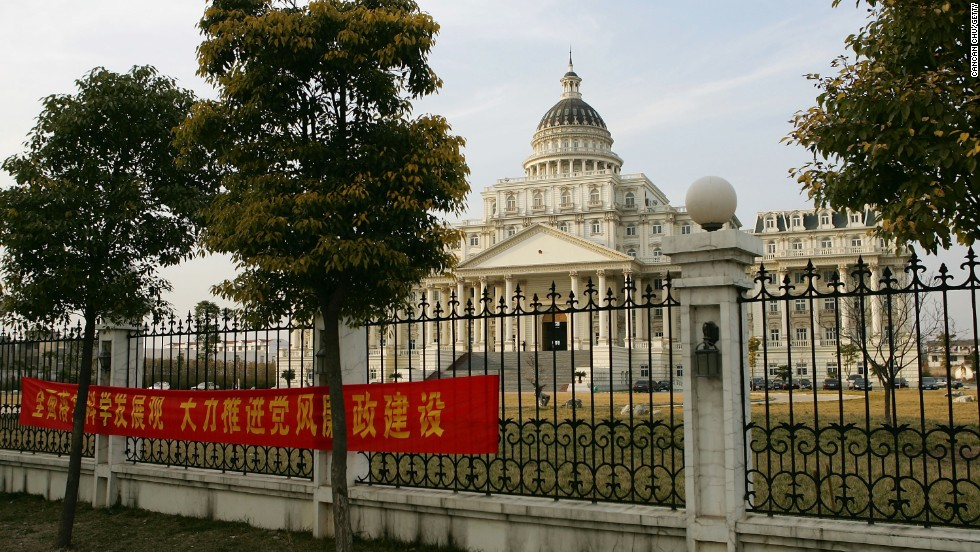 "A banner in front of a White House-inspired, 30 million RMB government office building reads, ""Pushing forward scientific development, vigorously implement party rules and reduce corruption."""