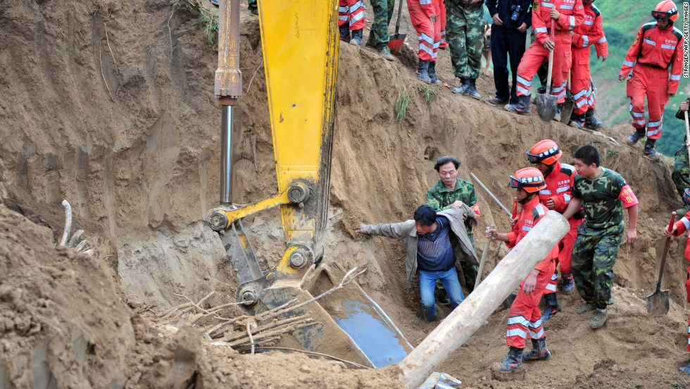 A man reacts after seeing his wife's shoes as rescuers search for earthquake survivors in Yongguang township, in northwest China's Gansu province, on Tuesday, July 23.