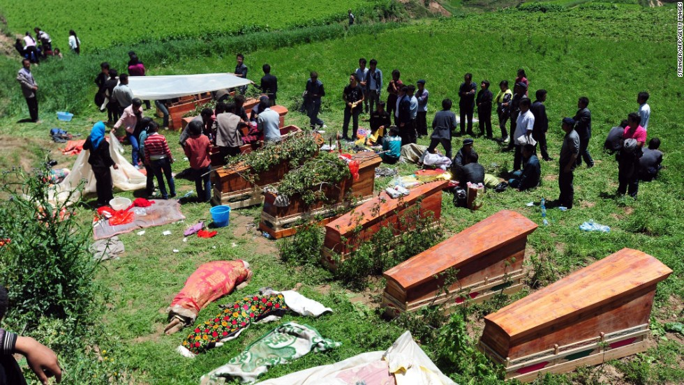 People gather to bury the dead in Yongguang, China, on July 23.