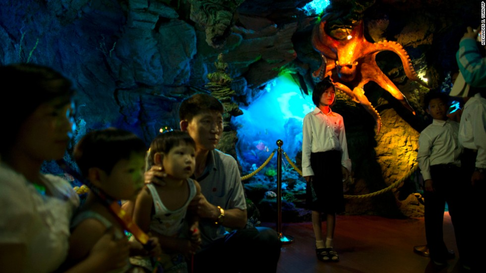 People pose for photos near a display model of an octopus as they visit a dolphin show facility at an amusement park in Pyongyang on Sunday, June 23.