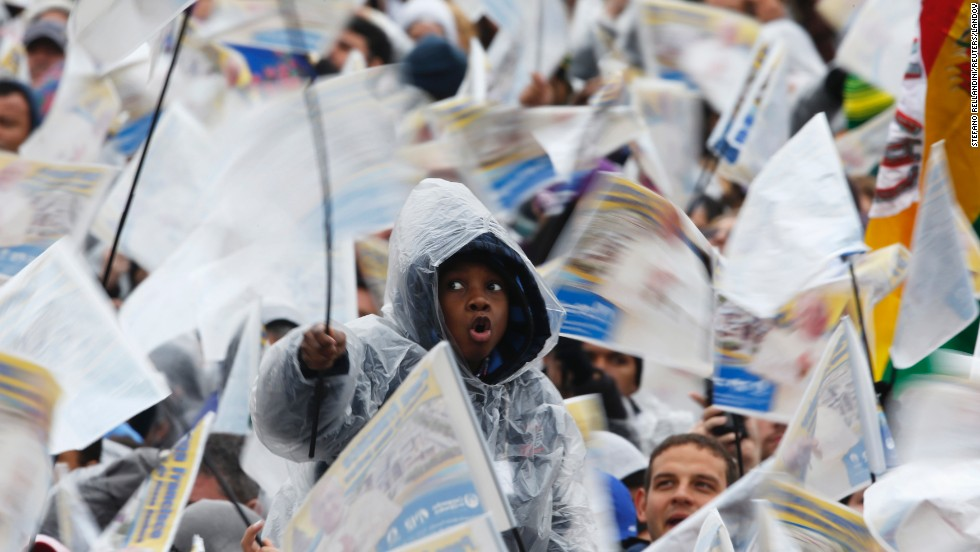 A boy waves a flag along with the other faithful to see the pope in Aparecida on July 24.