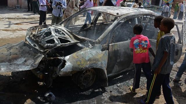 Somali children look at a burnt car after a bomb blast in Hamarweyne Market in Mogadishu on July 24, 2013.