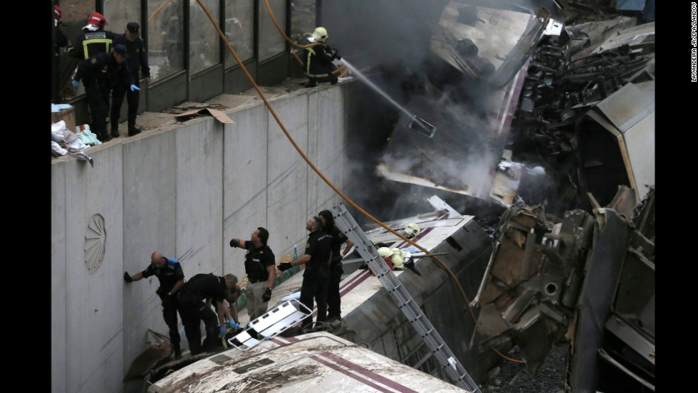 Emergency workers climb on top of the wreckage as they help free injured passengers from the crash.