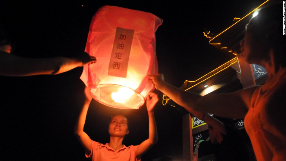 People pray for the earthquake victims in Laibin, China, on July 24.