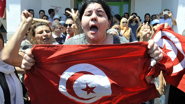 "Belkaeis Brahimi, the daughter of Tunisian opposition politician Mohamed Brahmi, shows a national flag shouting outside a hospital after her father was killed on July 25, 2013 in Ariana, outside Tunis. ""Mohamed Brahmi, general coordinator of the Popular Movement and member of the National Constituent Assembly, was shot dead outside his home in Ariana, "" state media announced. AFP PHOTO / FETHI BELAIDFETHI BELAID/AFP/Getty Images"