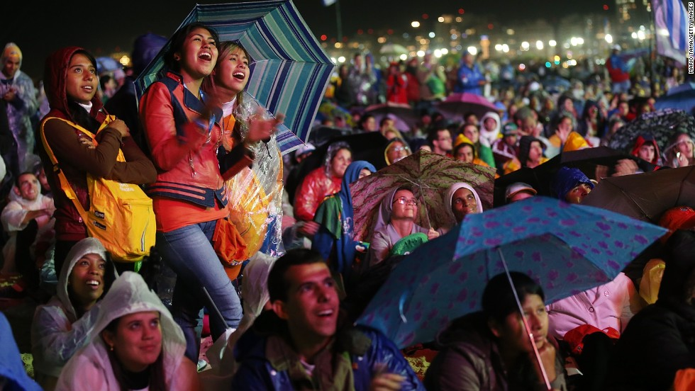 People watch the pope's beachfront service on a video screen on July 25.