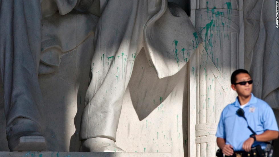 A U.S. Park Police officer stands guard next to the vandalized statue of Abraham Lincoln at the Lincoln Memorial in Washington on Friday, July 26. The memorial was closed to visitors after someone splattered green paint on the statue and the floor area.