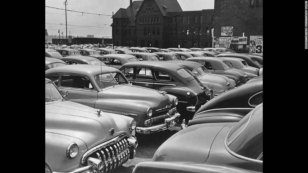 The American automobile industry has been centered in Detroit. Rows of these behemoths in a city parking lot around 1960 show the industry at its height.