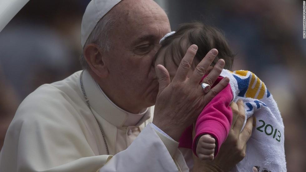 Pope Francis kisses a child in San Joaquin Square in Rio de Janeiro on July 26.
