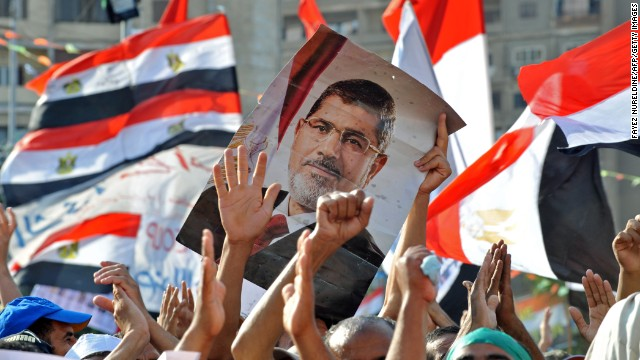 Egyptian supporters of deposed president Mohamed Morsy hold up his portrait and wave their national flag, as they continue to hold a sit in outside Cairo's Rabaa al-Adawiya mosque on July 24, 2013. Egypt's army chief General Abdel Fattah al-Sisi called for public rallies this week to give him a mandate to fight 'terrorism and violence,' as Morsi's supporters continue to protest against his ouster. AFP PHOTO/FAYEZ NURELDINE (Photo credit should read FAYEZ NURELDINE/AFP/Getty Images)