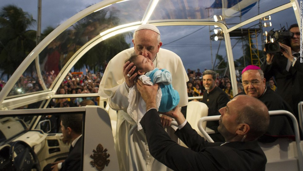 The pope blesses a child as he arrives at Copacabana beach in Rio de Janeiro, on July 26.