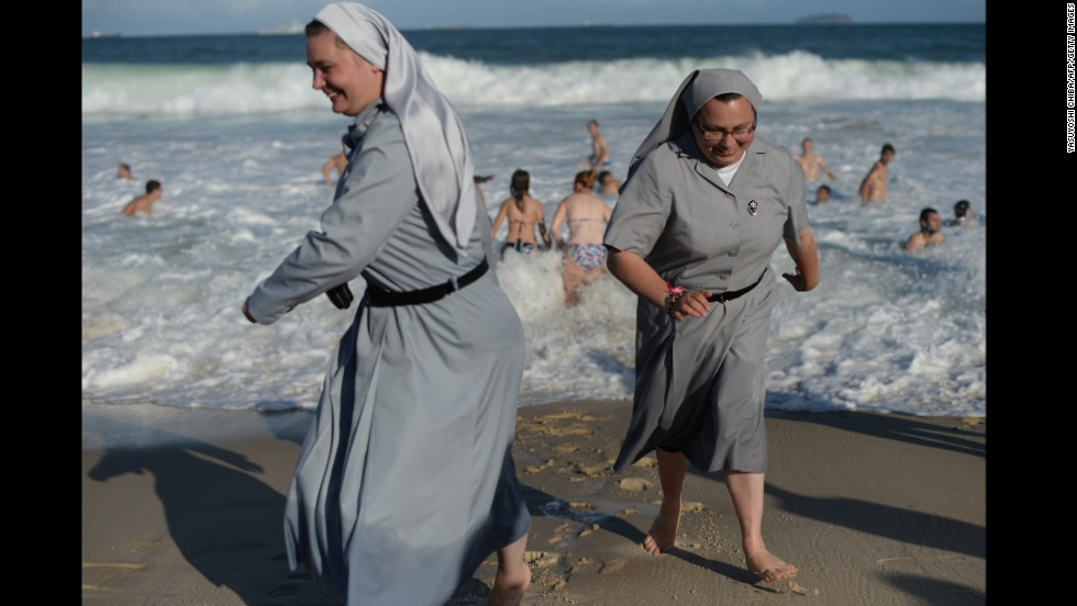Two Polish nuns laugh as they enjoy the surf along with the massive crowd gathering on Copacabana Beach on July 27.