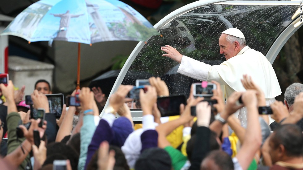 """Pope Francis waves to people from the """"Popemobile"""" in Rio de Janeiro on July 27."""