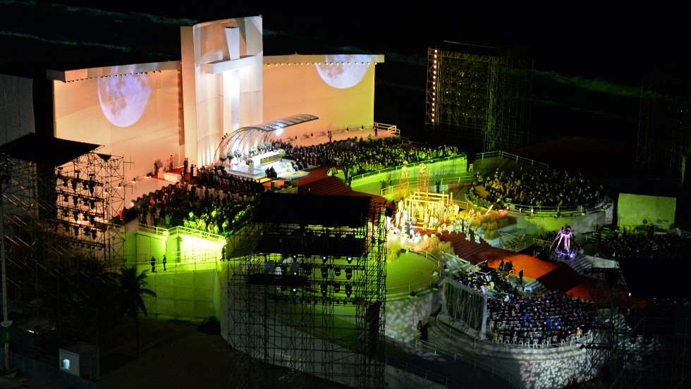 Pope Francis address the crowd from a brightly lit stage.