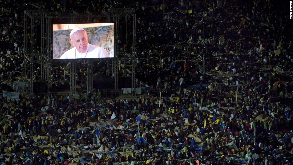 The pope's image is broadcast on screens throughout the crowd.