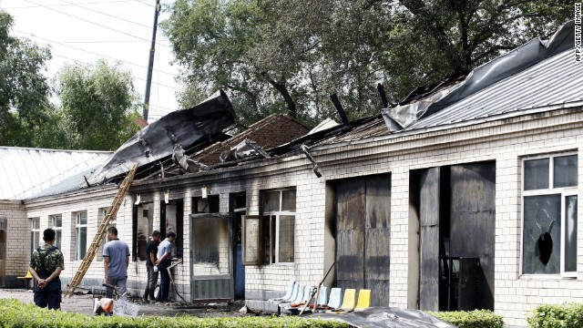 Investigators examine nursing house set alight in Hailun, northeast China's Heilongjiang province on July 26, 2013.