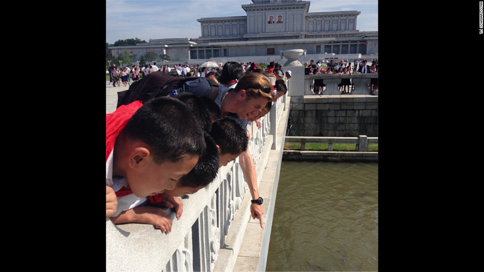 """Elsewhere, Watson enjoys a contemplative moment with North Korean schoolchildren enjoying the carp pools by the<a href=""""http://instagram.com/p/cLfanRhqJS/ """" target=""""_blank""""> Kumsusan Palace of the Sun</a>. """"[It was a] fascinating and strange experience,"""" Watson reflected of his time in the country."""