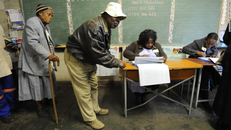 Zimbabweans arrive to vote at a polling booth in a school in Harare on July 31.