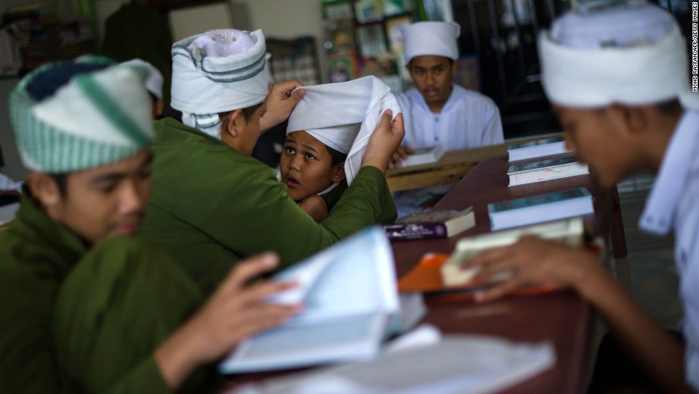 A boy helps his friend put on a turban during their Quran lesson at a mosque in Ampang, Malaysia, on Tuesday, July 30.