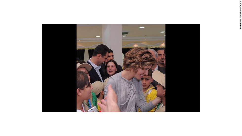 Asma al-Assad shows affection to the children surrounding her.