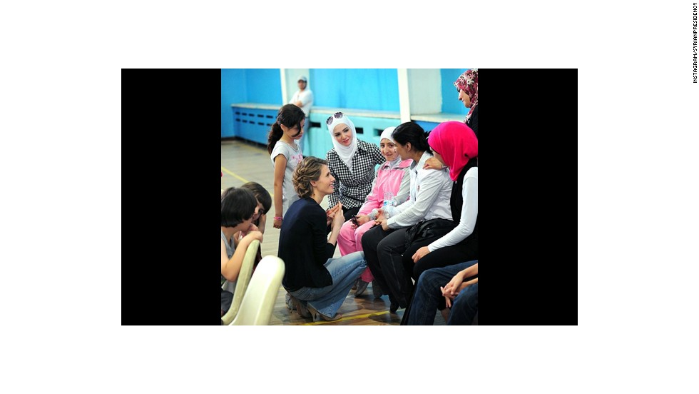 Asma al-Assad kneels before a group of women. Photo after photo on the president's Instagram feed shows al-Assad and his wife as caring -- and apparently being loved by those they interact with.