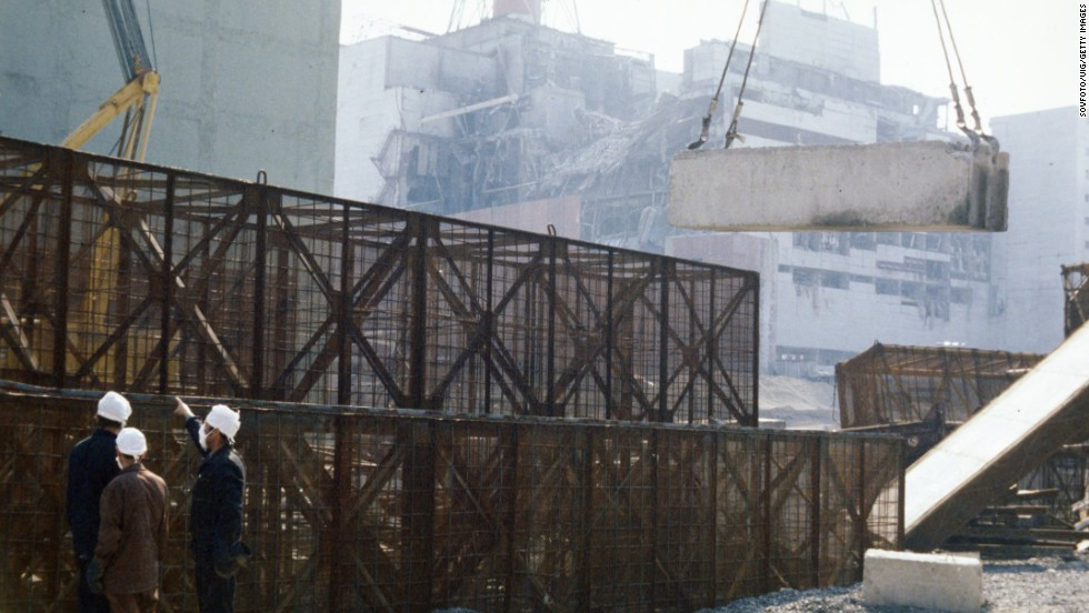 Construction crews build a containment wall around the damaged unit four reactor in August 1986.