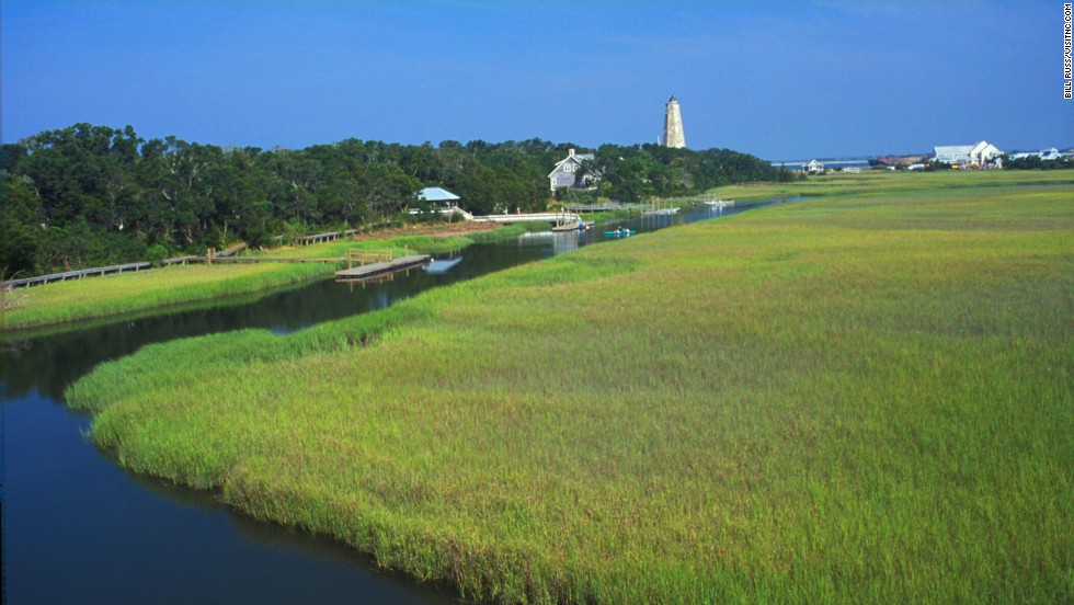 Bald Head Island is the southernmost of North Carolina's cape islands. Most of its 12,000 acres is set aside as natural preserves. The island includes the salt marsh and paddle trail, with the historic Old Baldy lighthouse and the beach shown in the distance.
