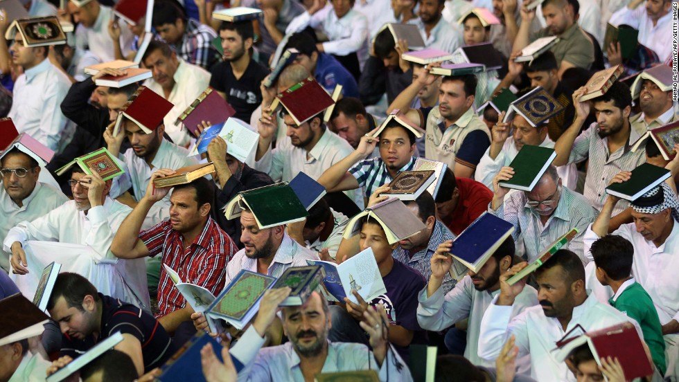Worshipers place the Quran over their heads in an act of penitence as they attend a Lailat al-Qadr, or Night of Destiny, prayer in the Imam Musa al-Khadim shrine in Baghdad, Iraq, on Thursday, August 1.