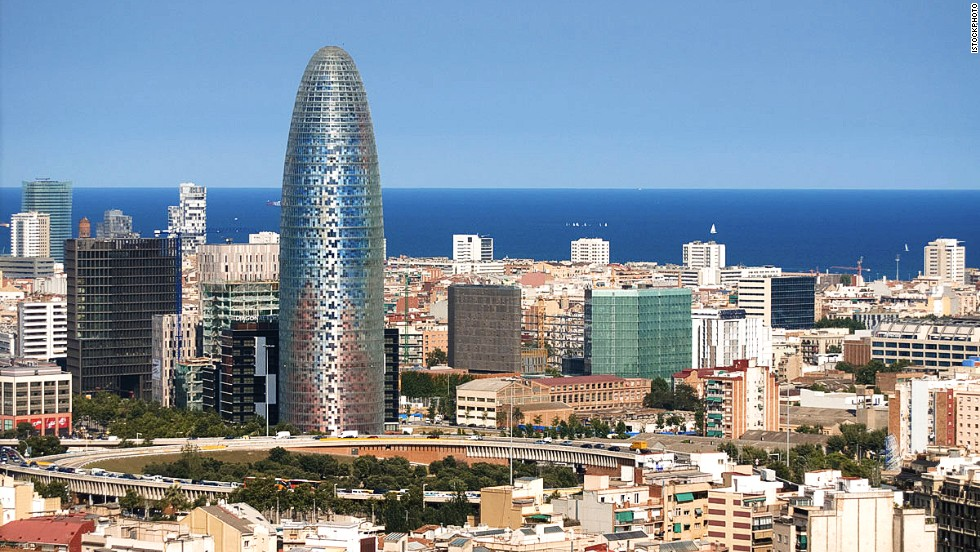 <strong>Height</strong>: 142 meters.<br /><strong>Cost to build</strong>: $130 million.<strong><br />Completion date</strong>: 2004.<br /><strong>Fast fact</strong>: The design is inspired by a geyser, shooting up to touch the sky above Barcelona.