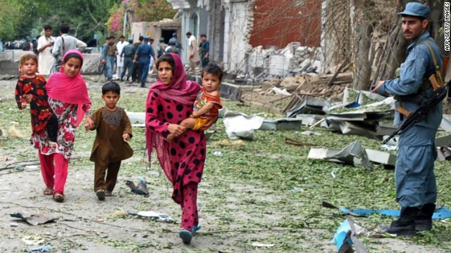 An Afghan policeman looks on as children flee from the site of a suicide attack in front of the Indian consulate in Jalalabad on August 3, 2013.