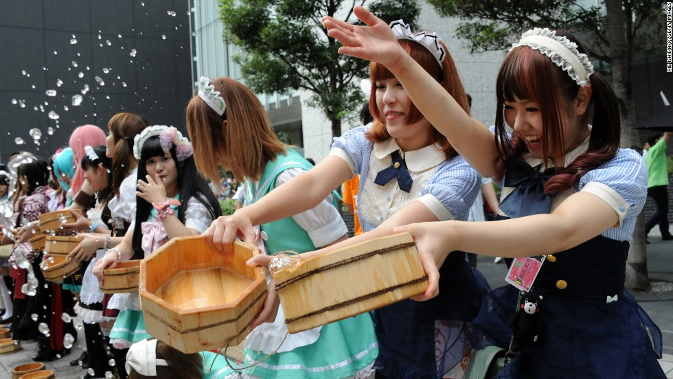 Women in maid costumes throw water to the ground in the Akihabara shopping district in Tokyo on Saturday, August 3. They were taking part in an annual summer event to cool off the street.