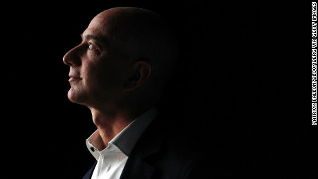 Jeff Bezos, chief executive officer of Amazon.com Inc., watches a video of the new Kindle Fire HD tablet at a news conference in Santa Monica, California. Photographer: Patrick Fallon/Bloomberg via Getty Images