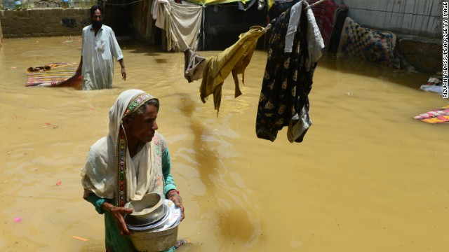 A Pakistani woman walks through floodwaters following heavy monsoon rain in Karachi on August 5, 2013.