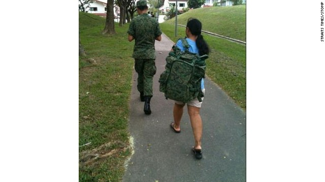 This picture of a maid carrying a SIngapore national serviceman's backpack went viral in 2011