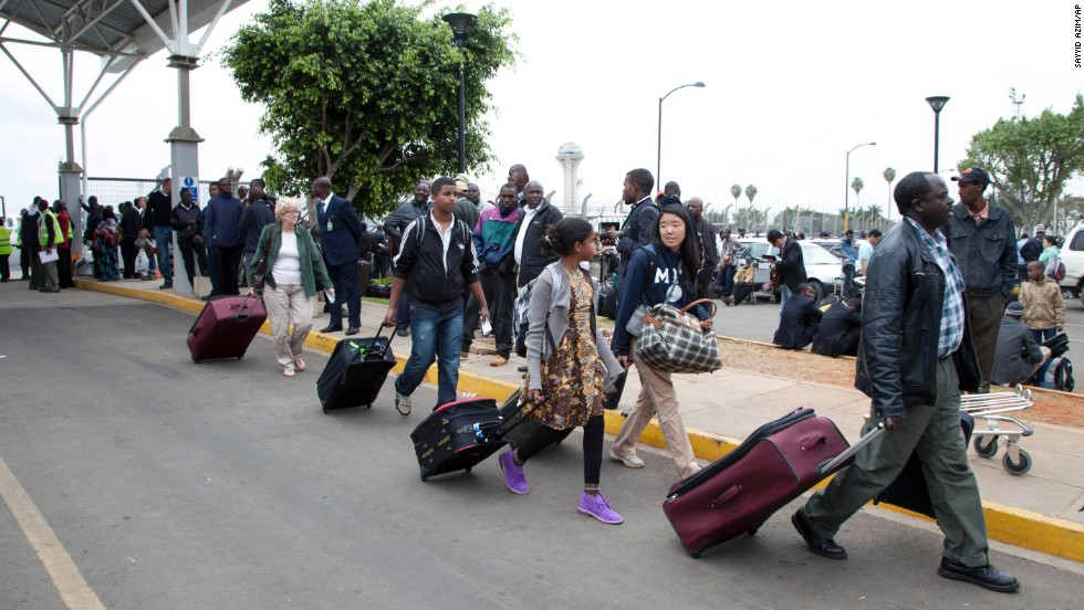 Travelers walk to be taken to hotels after the airport initially was closed August 7 following the fire. <br />