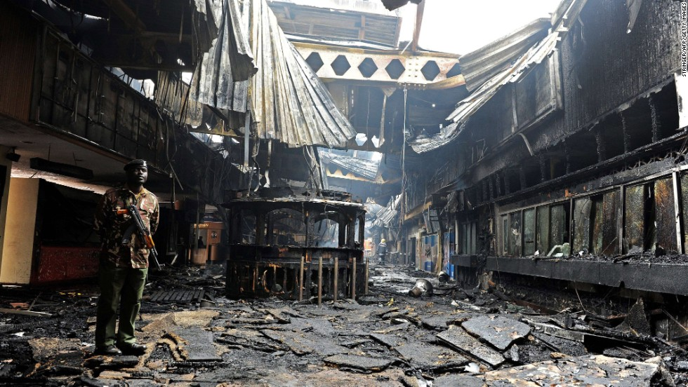 A soldier stands among the debris August 7. The cause of the fire is uknown, but security is being ramped up at the airport, an official said.