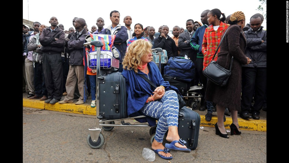 Stranded passengers wait outside the airport August 7.