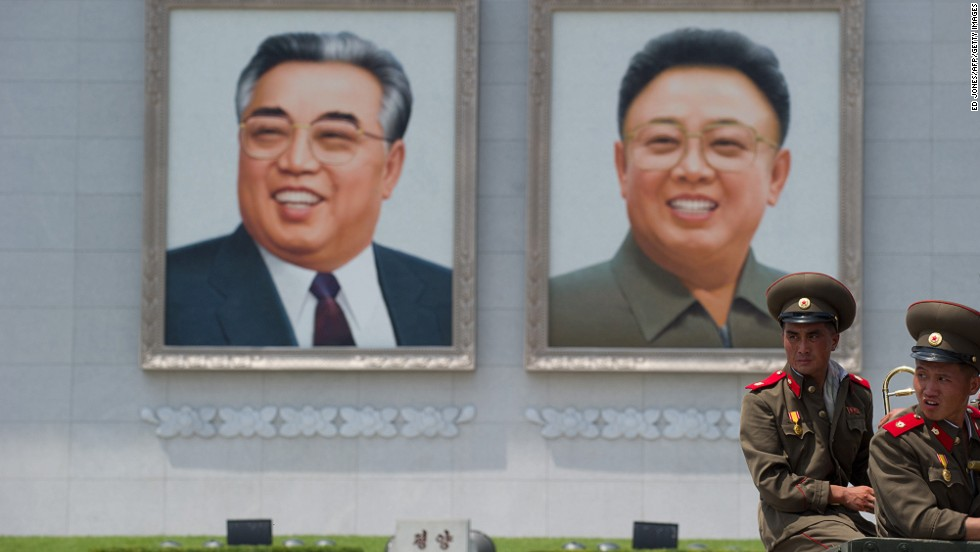 North Korean soldiers sit on the back of a truck on Kim Il-Sung square before portraits of former leaders Kim Il-Sung (l) and Kim Jong-Il (r).