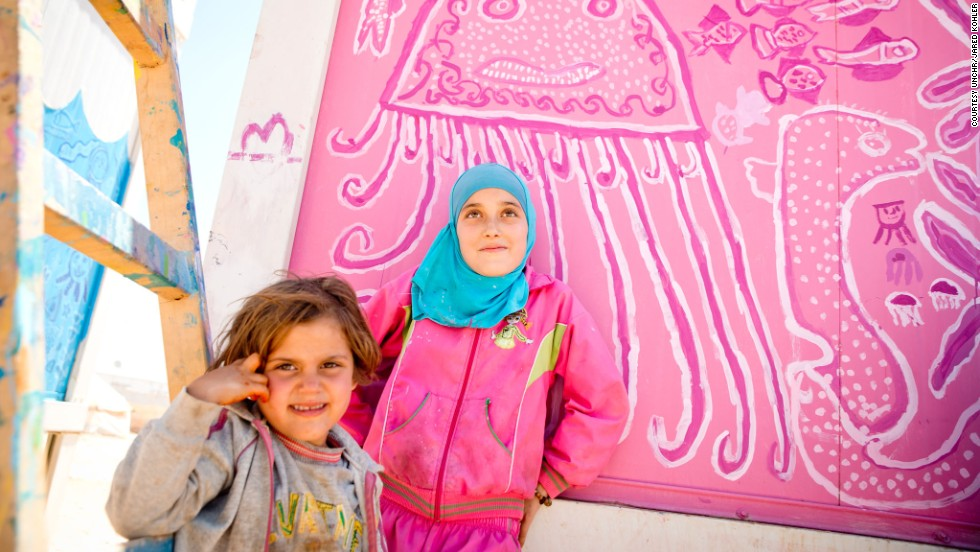 "Two young Syrian girls at the Za'atari refugee camp in Jordan paint decorations on walls of the community bathrooms. ""Doing this project helps us keep our minds off fasting,"" says 12 year old Sula (right), a refugee from a village outside Dara'a."