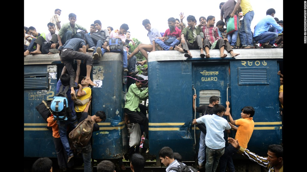 Bangladeshis cram onto a train as they rush home to their respective villages to be with their families ahead of the Muslim festival of Eid al-Fitr on Thursday, August 8. Ramadan commemorates the revelation of the Quran, the sacred religious text of Islam, by the angel Gabriel to the Prophet Mohammed, according to Islamic tradition.