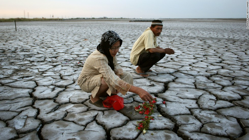 An Indonesian woman offers flowers on dried volcanic mud for family members who died during a volcano eruption in Sidoarjo in eastern Java as Indonesians mark Eid al-Fitr with pilgrimages to cemeteries to remember their dead.